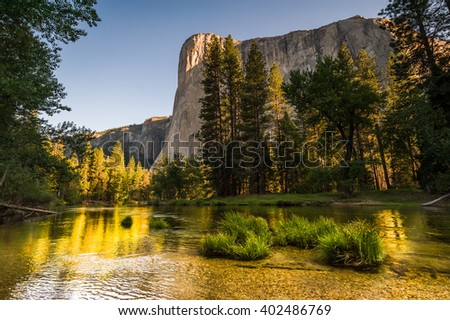Beautiful golden sunrise on El Capitan with relfection in Merced River.