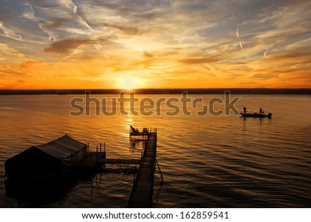 Beautiful golden sunrise over Lake Cayuga in New York with dock and fishermen. - stock photo