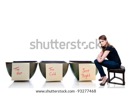 Beautiful Goldilocks woman with bowls of too hot, too cold and just right porridge. - stock photo