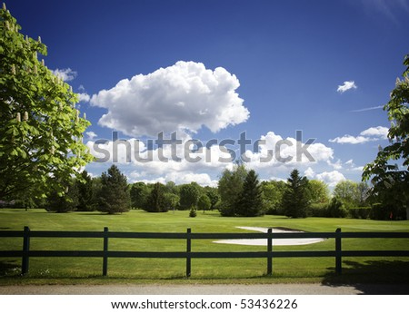 Beautiful golf course with bunker in front of green and cloudy sky. - stock photo