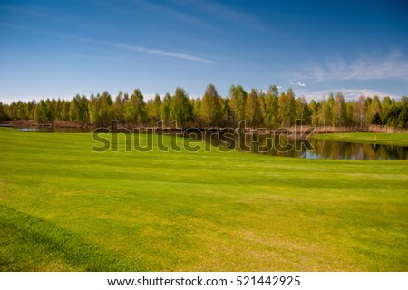 Beautiful golf course with gorgeous green and pond.  Golf field with lake in sunny day. Background of golf field.