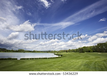 Beautiful golf course with lake, fairway and beautiful cloud formation. - stock photo