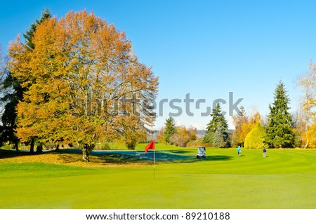 Beautiful golf place with gorgeous green an yellow Fall trees. - stock photo
