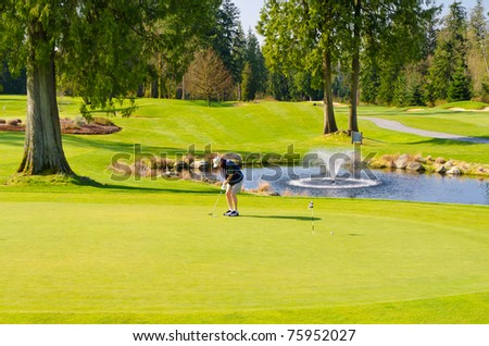 Beautiful golf place with gorgeous green and pond - stock photo