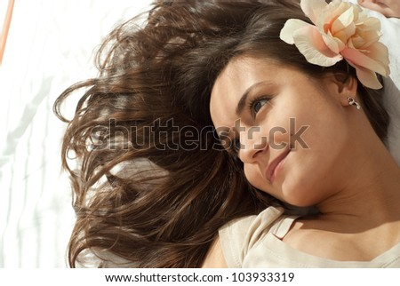 Beautiful good female lying on a pillow on a light background - stock photo