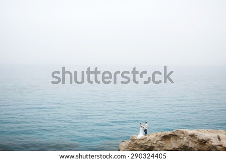 beautiful  gorgeous blonde bride  and stylish groom on rocks, on the background of a sea, wedding ceremony  on cyprus