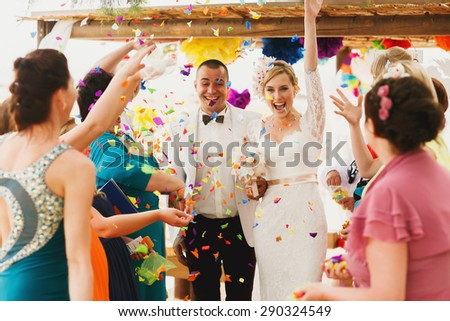 beautiful  gorgeous blonde bride  and stylish groom under confetti, hawai  colorful sand ceremony  on cyprus - stock photo