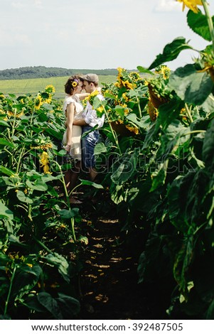 beautiful gorgeous bride and stylish handsome groom, rustic couple in a sunflower  field kissing