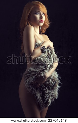 Beautiful, gorgeous, ginger girl cover her nude body with fluffy fur. She has got amazing bracelet and earrings.