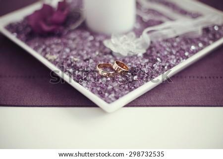 beautiful gorgeous golden wedding rings on violet gemstone box - stock photo