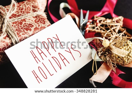 beautiful gorgeous present in design paper with ribbons, toys and card, happy holidays text - stock photo