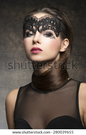 Beautiful, gorgeous, stunning brunette woman with hairstyle near neck and transparent mask on the face, make up is dark with pink lips. She is wearing black transparent top. - stock photo