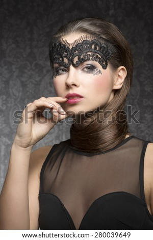 Beautiful, gorgeous, stunning brunette woman with transparent mask on the face and nice hairstyle near the neck, make up is dark with pink lips. She is wearing black transparent top. - stock photo