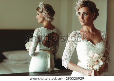 beautiful gorgeous stylish bride with orchids getting prepared in the morning in the room - stock photo