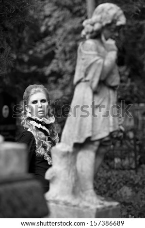 Beautiful gothic girl at cemetery. Black-and-white photo.