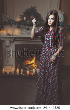 Beautiful gothic girl raised her hand with scissors. She looks like a witch. - stock photo