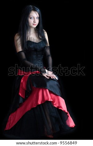 Beautiful gothic girl wearing vivid dress isolated on black - stock photo