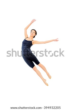 Beautiful graceful ballet dancer in black ballet leotard posing at studio. Jump, movement. Art concept. Isolated over white. - stock photo