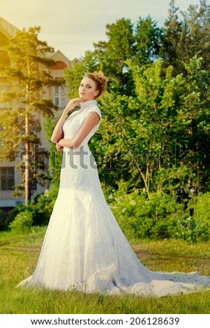 Beautiful graceful bride in a summer park. Wedding dress and accessories.  - stock photo