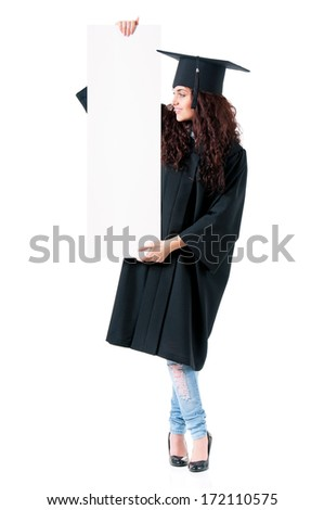 Beautiful graduate girl student in mantle showing blank board, isolated on white background - stock photo