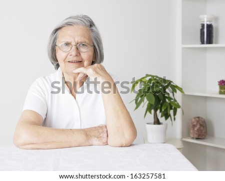 Beautiful grandmother sitting at table with hand on her chin and looking at camera. - stock photo