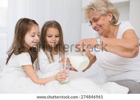 Beautiful grandmother with granddaughter drinking milk, healthcare concept.