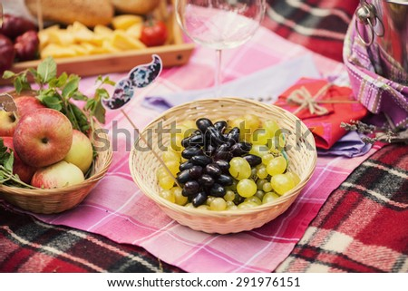 Beautiful grapes with different food lies in the basket on the plaid