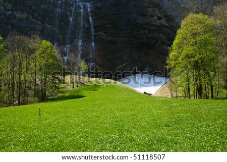 Beautiful grass land with waterfall - stock photo