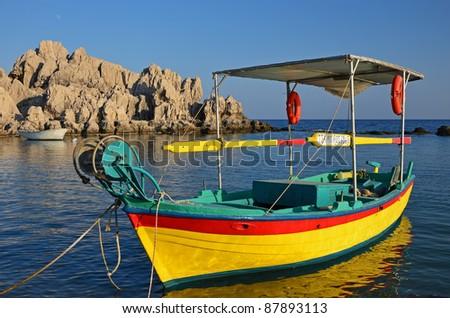 Beautiful greek fishing boat at sunset time, Rhodes island - stock photo