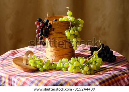 Beautiful green and blue grapes in a basket from the bark - stock photo