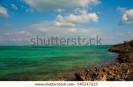 Beautiful green and blue waters in the islands of the bahamas, framed by a rocky limestone coastline.  copy space available int he sky or on the water. - stock photo