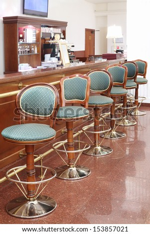 Beautiful green classic chairs stand next to bar counter in empty room. - stock photo