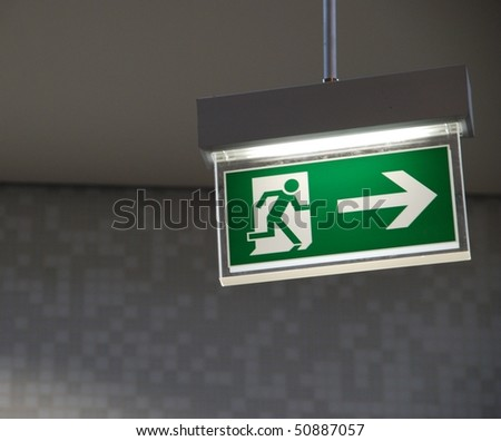 beautiful green emergency exit sign hanging on a ceiling - stock photo