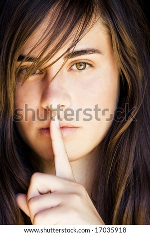 Beautiful green eyed woman in silence gesture. - stock photo