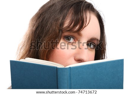 Beautiful green eyes of young brunette woman looking up from behind a book she is reading. - stock photo