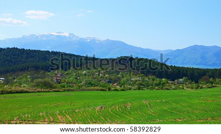 Beautiful green field and mountain landscape with trees in April day in Bulgaria