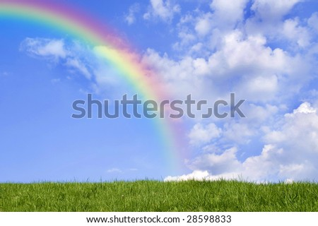 Beautiful green grass against blue sky and rainbow. - stock photo