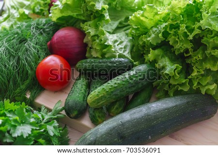 Beautiful green greens with cucumbers and red tomato and onions.