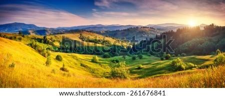 Beautiful green hills glowing by sunlight at twilight. Dramatic scene. Colorful sky. Carpathian, Ukraine, Europe. Beauty world. - stock photo