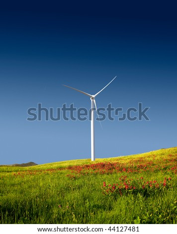 Beautiful green meadow with a wind turbine generating electricity