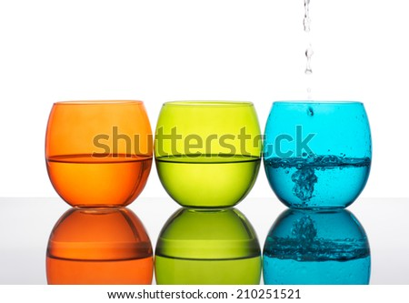 Beautiful green orange and turquoise glasses of water, one being poured. Hydration, healthy living.. - stock photo