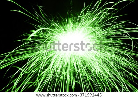 Beautiful green sparkler on black background, close up - stock photo