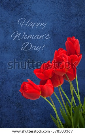 Beautiful Greeting Card with text Happy Women's Day for International Women's Day, March 8. Red Tulips Flowers lie on navy blue background. Vertical Image