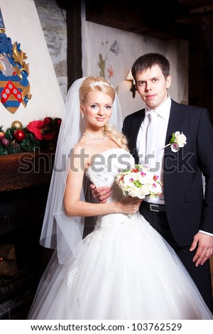 beautiful groom and bride in interior on wedding day - stock photo