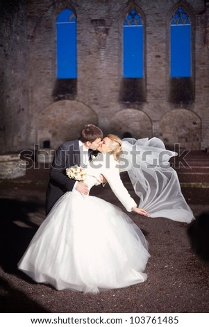 beautiful groom and the bride in stone court yard of  medieval castle - stock photo