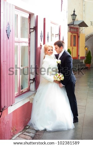 beautiful groom and the bride on the street of old Tallinn - stock photo