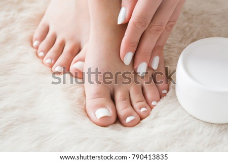 Beautiful groomed woman's hand applying a feet moisturizing cream. Bare feet on the fluffy mat. Cares about clean and soft legs skin in winter time. Healthcare concept.
