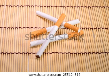 beautiful group of cigarettes set up on bamboo mat - stock photo
