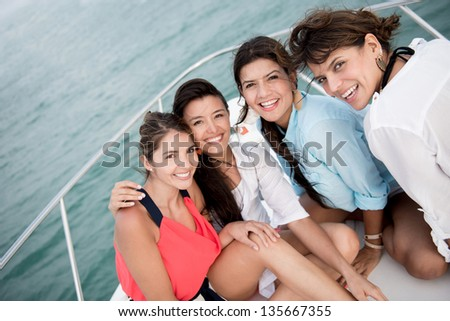 Beautiful group of girl friends in a boat having fun - stock photo