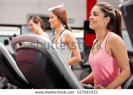 Beautiful group of young women exercising on a treadmill at the gym - stock photo